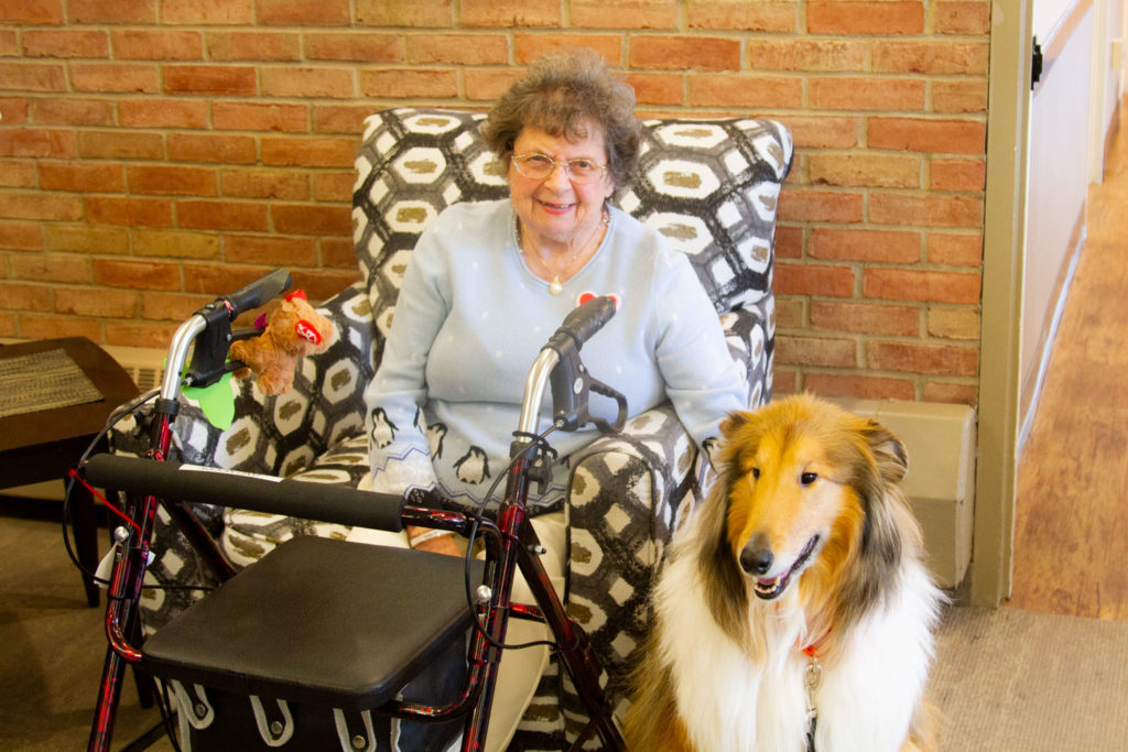 Brookcrest resident sitting with service dog Murphy