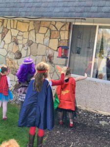 children dressed as superheros waving through a window